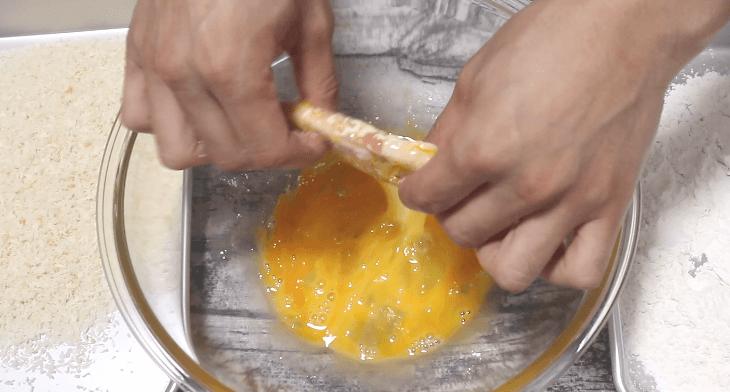 小麦粉をつけたロース肉に卵をつける